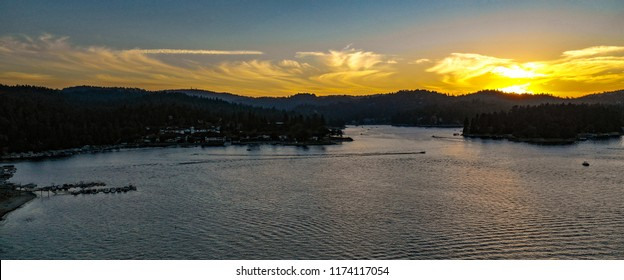 Aerial view of Lake Arrowhead at dusk with green trees, blue water and sky, yellow, gold, orange sunset in the San Bernardino Mountains, California