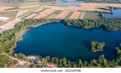 Aerial view of the lake Bela Crkva, Serbia uninhibited island. Aerial Drone view of colorful top of the agricultural fields and a lake at summer. Aerial view of lake.