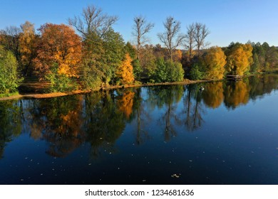 Aerial view of the lake and the bright yellow forest is  reflected in it. Boat with fishermen in the middle of the lake. Autumn landscape