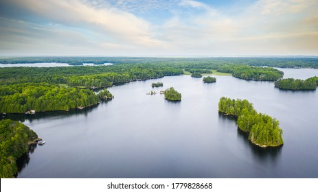 Aerial view of a lake in Canada. Multiple islands and a cloudy sky are visible in the image. The picture was captured with a drone.