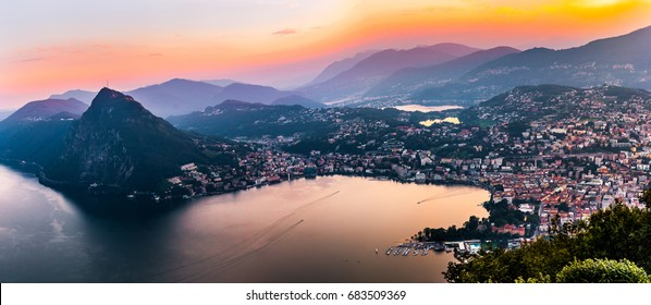 Aerial view of the lake Lugano surrounded by mountains and evening city Lugano on during dramatic sunset, Switzerland, Alps. Travel