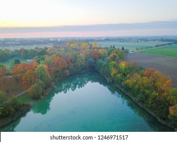 Aerial view of lake and misty autumn fields in the background