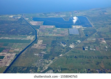 Aerial view of Lake Okeechobee in Florida, with the St. Lucie River and canal, plus an electricity producing power plant, with cooling pond, and solar panels.