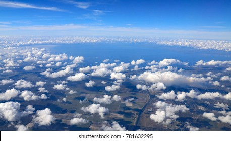 Aerial view of Lake Okeechobee in South Florida, surrounded by clouds, with no clouds right over the lake, which creates it's own weather system.