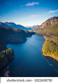 Aerial view of Lake surrounded by Trees and Mountains near Vancouver, British Columbia, Canada