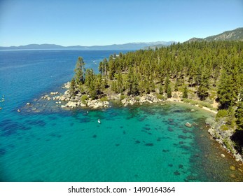 Aerial view of Lake Tahoe's shore during the summer season. Clear blue water and beautiful beach