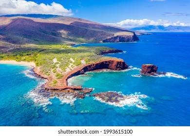 Aerial view of Lanai, Hawaii featuring Hulopo'e Bay and beach, Sweetheart Rock (Pu'u Pehe), Shark's Bay, and the mountains of Maui in the background.