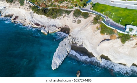 Aerial view of landmark big white chalk rock at Governor's beach, Limassol, Cyprus. Steep stone cliffs, deep blue sea waves crushing in coves and dark sand next to Kalymnos fish restaurant from above.