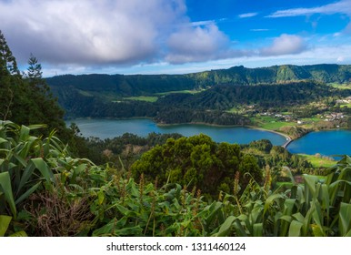Aerial view of landscape with green and blue crater lakes of Lagoa Azul and Lagoa Verde and Sete Cidades village in the crater of dormant volcanoes, on Sao Miguel island, Azores, Portugal.