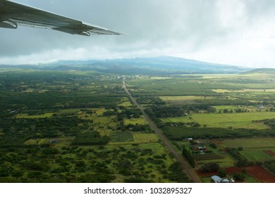 Aerial view of the landscape of the island of Molokai in Hawaii, showing the wing of a small airplane