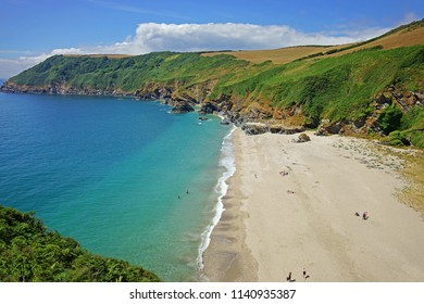 Aerial view of Lantic bay and its beautiful turquoise water with people enjoying a beautiful sunny summer day, this is a secluded beach on the South coast of Cornwall, England, UK