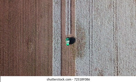 Aerial view of a Large green Cotton picker working in a field.