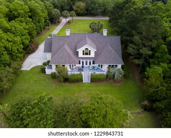 Aerial view of large home with new roof on wooded grassy property