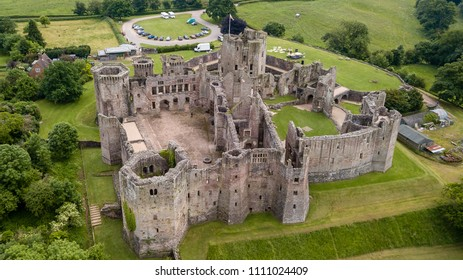 Aerial view of a large medieval castle showing the turrets, walls and moat (Raglan Castle, South Wales)