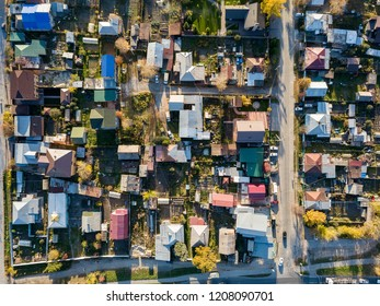 Aerial view of a large number of small houses on the outskirts of the city on an autumn afternoon during Indian summer with the road and cars