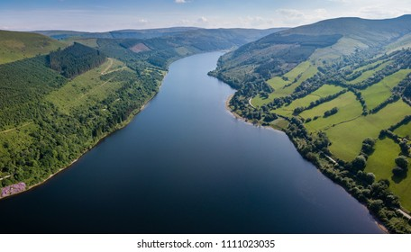 Aerial view of a large reservoir in a deep valley surrounded by green fields (Tal-y-Bont, Wales)