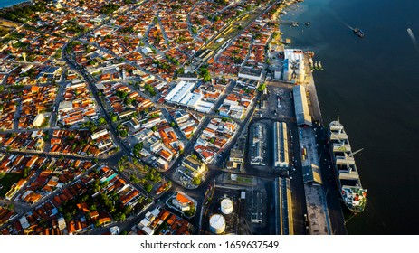Aerial view of a large river with a big container ship parked at a dock in Joao Pessoa, Brazil