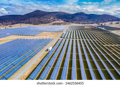Aerial view of a large solar farm for renewable energy supply in Canberra, Australia on a countryside mountain landscape background