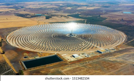 Aerial view of a large solar thermal plant uses mirrors that focus the sun's rays on a collection tower to produce renewable and pollution-free energy.