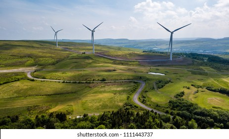 Aerial view of large wind turbines on a rural hillside in Wales