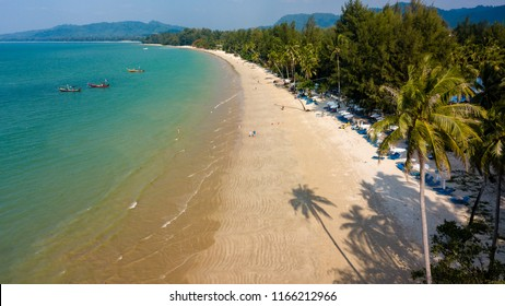 Aerial view of late afternoon shadows being cast onto a beautiful tropical sandy beach in Thailand (Coconut Beach, Khao Lak)