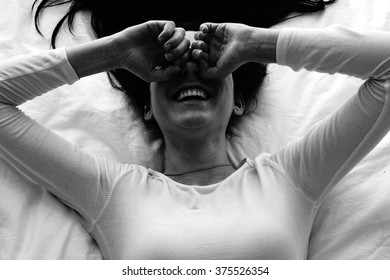 Aerial view of laughing woman on bed.