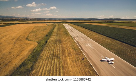Aerial view of a light aircraft, taking off at the runway of a small countryside airfiled