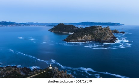 Aerial view of lighthouse cliffs sticking out of blue water of ocean in twilight of San Martiño Island in the Cies Islands, National Park Maritime-Terrestrial of the Atlantic Islands, Galicia, Spain