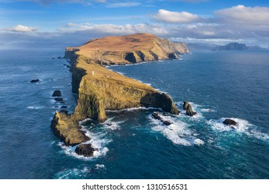 Aerial view of a lighthouse, dramatic cliffs and crashing waves along the island of Mykines in the Faroe Islands.