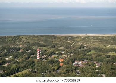 Aerial view of the lighthouse (Westerlichttoren) of the village of Burgh Haamstede on a island at Zeeland, Holland. On the clear horizon the Northsea and a line of cumulus clouds.