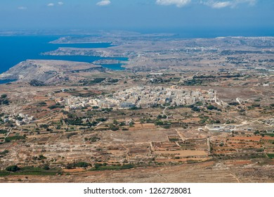 Aerial view of L-Imgarr (Mgarr, Mġarr, Mgiarro) town, Northern region, Malta island. Rich farmland and vineyards around. Panoramic photo of Malta from above toward north-west and Gozo island.