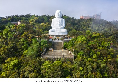 Aerial view of Linh Ung Pagoda with a giant buddha statue among green trees and sea clouds floating on the top of Ba Na mountain. Near Golden bridge. Da Nang, Vietnam