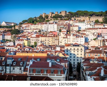 Aerial view of Lisbon in Portugal showcasing its historic buildings, cobblestone streets, and the Castelo de Sao Jorge at the top.