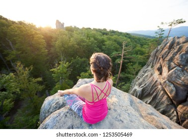 Aerial view of lit by summer sun young slim sporty woman sitting on top of huge rock, doing yoga on green trees tops forest background in the morning. Sport, gymnastics and fitness concept. Siddhasana