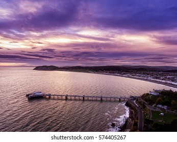 Aerial view of Llandudno pier and bay in North Wales at sunrise.
