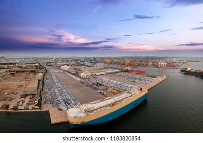 Aerial view of logistics concept commercial vehicles, cars and pickup trucks waiting to be load on to a roll-on/roll-off car carrier ship at Laem Chabang dockyard in Chonburi Province, Thailand