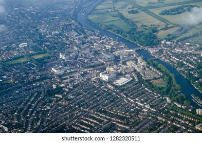 Aerial view of the London Borough of Kingston-Upon-Thames in West London with the River Thames flowing past the historic suburb and the grounds of Hampton Court Park beyond.  Early on a summer morning