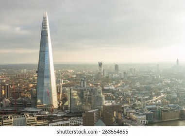 Aerial view of London with The Shard skyscraper and Thames river at sunset with grey clouds in the sky
