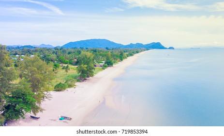 Aerial view long white beach of Khanom, Nakhon Si Thammarat, Thailand with green tree along the beach and mountain