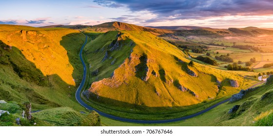 Aerial view of long winding road leading through mountains in the Peak District.