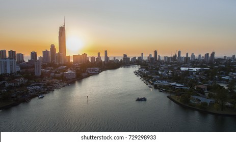 Aerial view looking down Nerang river of Surfers Paradise cityscape and Isle of Capri waterfront properties at sunrise.