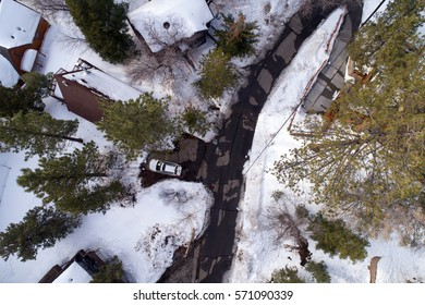 Aerial View Looking Down on Snow Covered Cabins Street and Car