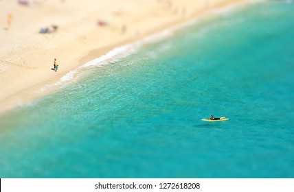 An aerial View looking down onto the white sandy beach and turquoise green ocean at Porthcurno beach in Cornwall UK.