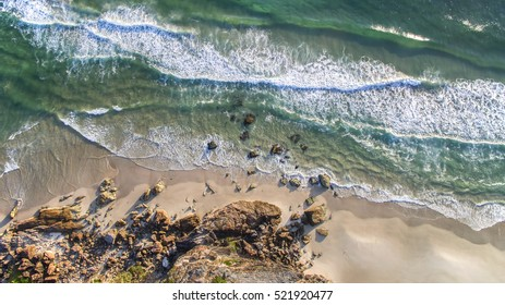 Aerial view looking down at the rocks of Miami Headland as the sunrise glow hits the foreshore. Gold Coast, Australia