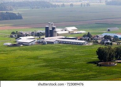 Aerial view looking at a large farm surrounded by farmland and crops in rural Quebec, Canada, late summer early fall season.