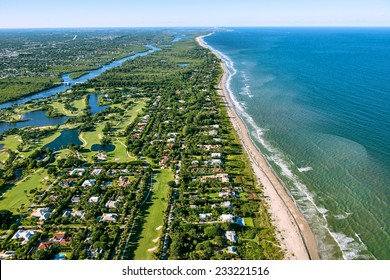 aerial view looking north, of Jupiter and Hobe Sound, Florida, along the Atlantic Ocean coast, lined by the beach and dotted by luxury homes golf courses