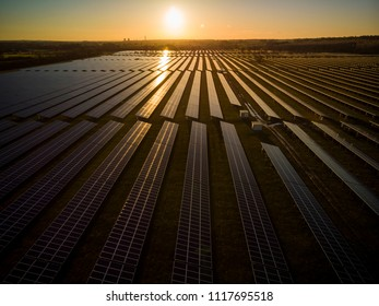 Aerial view looking out onto a large solar farm at sunrise with light reflecting off the panels