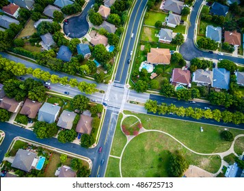 Aerial View Looking Straight Down Above Suburban Neighborhood in North Austin / Roudn Rock , Texas at an All way stop with community park modern layout and Cul De Sac Rooftops and Homes
