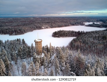 Aerial view of the lookout tower in winter landscape at Aulanko nature reserve park in Hämeenlinna, Finland. Frosty trees and snowy forest around an icy lake.