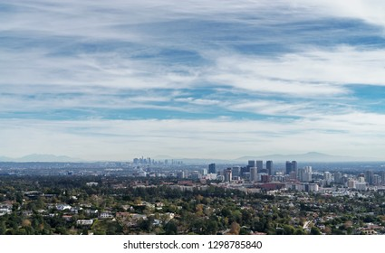 Aerial view of Los Angeles, California. View toward the Wilshire district and downtown. Hills in background. Blue sky and clouds. Room for text.